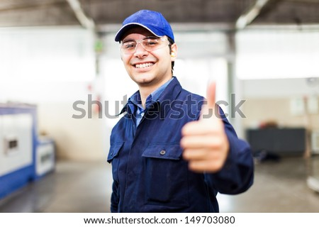Portrait of a smiling worker in a factory - stock photo