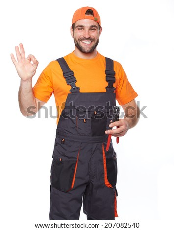 Portrait of a smiling worker in blue uniform holding pliers, isolated on white background - stock photo