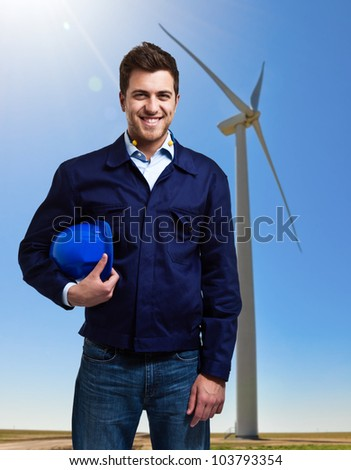 Portrait of a smiling worker in front of a wind power plant - stock photo