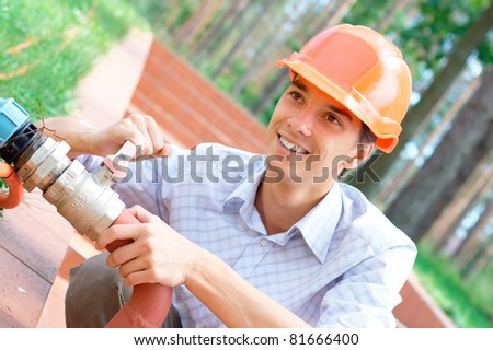 Portrait of a smiling worker repairing a pipe outdoors with copy space