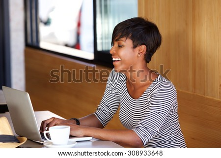 Portrait of a smiling young african american woman using laptop - stock photo