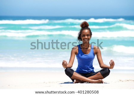 Portrait of a smiling young african woman sitting outdoors at the beach in yoga pose - stock photo
