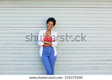 Portrait of a smiling young african woman with arms crossed standing against a wall - stock photo