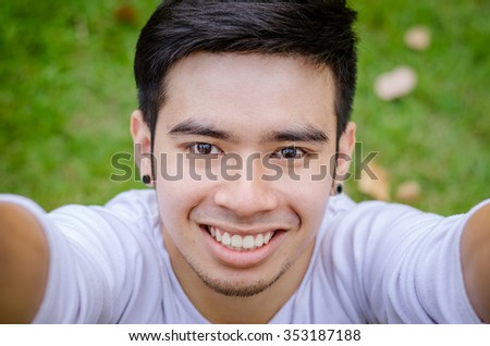 Portrait of a smiling young asian man making selfie photo in park