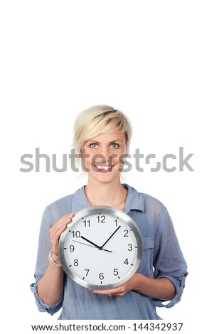 Portrait of a smiling young blond woman holding a clock against white background