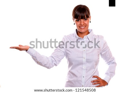 Portrait of a smiling young business female holding out her right palm and showing you copyspace on white background - stock photo