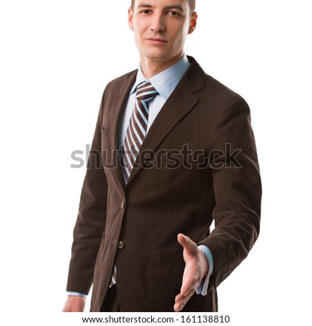 Portrait of a smiling young business man offering a welcoming hand isolated on white background - stock photo