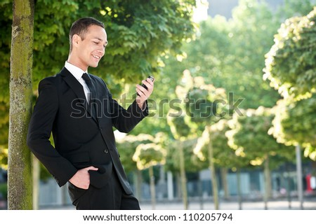 Portrait of a smiling young business man outdoors wearing a black suit, looking at his mobile phone and reading a text message. - stock photo