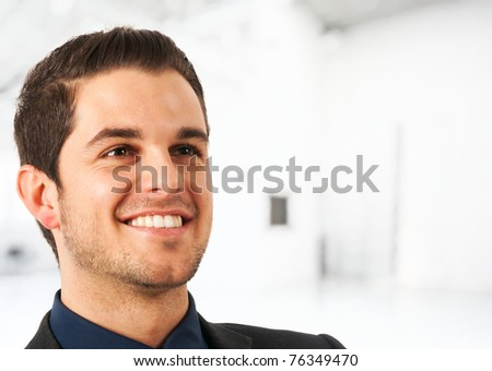 Portrait of a smiling young businessman. Blurred bright background.