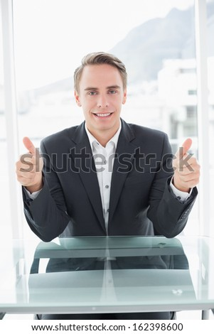 Portrait of a smiling young businessman gesturing thumbs up at office desk