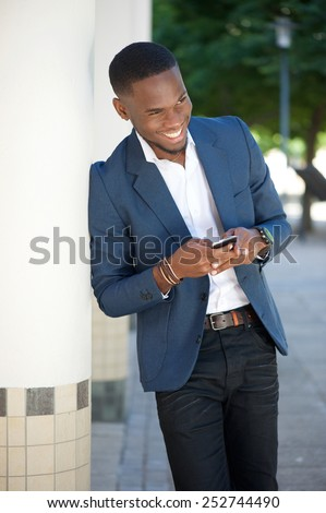 Portrait of a smiling young businessman sending text message by cellphone