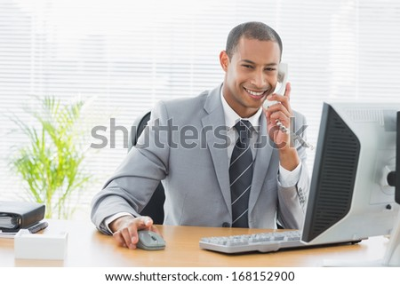 Portrait of a smiling young businessman using computer and phone at office desk - stock photo