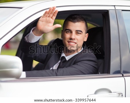 Portrait of a smiling young businessman waving while driving a car - stock photo