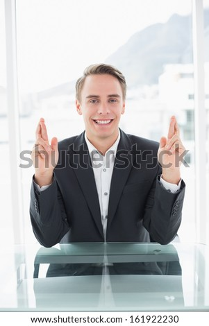 Portrait of a smiling young businessman with fingers crossed sitting at office desk