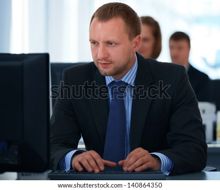Portrait of a smiling young businessman working on computer at office with his colleagues - stock photo