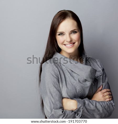 Portrait of a smiling young businesswoman on gray studio background, wearing gray jacket with long brunette hair - stock photo