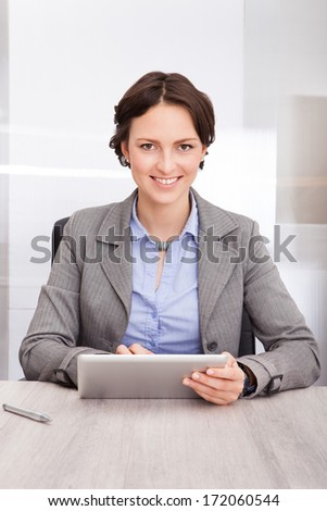 Portrait Of A Smiling Young Businesswoman Using Digital Tablet - stock photo