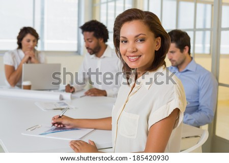 Portrait of a smiling young businesswoman with colleagues in meeting at office