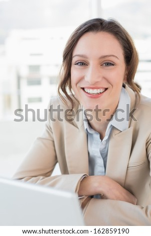 Portrait of a smiling young businesswoman with laptop in a bright office - stock photo