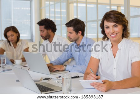 Portrait of a smiling young businesswoman writing notes with colleagues in meeting at the office
