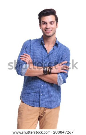 portrait of a smiling young casual man standing with arms folded on white background