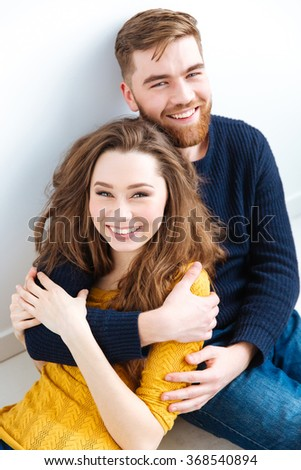 Portrait of a smiling young couple looking at camera - stock photo