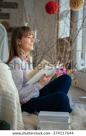 Portrait of a smiling young cute lady reading a book lying and relax on the floor in a bright big white room near window - stock photo