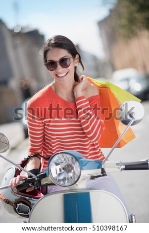 Portrait of a smiling young fashionable woman on a vintage scooter in the city, she holds shopping bags on her shoulder
