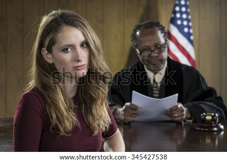 Portrait of a smiling young female attorney with older black male judge in courtroom - stock photo