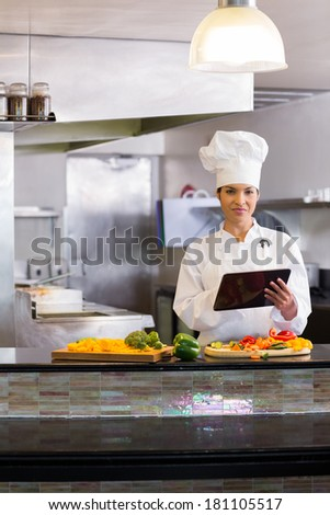 Portrait of a smiling young female chef using digital tablet while cutting vegetables in the kitchen