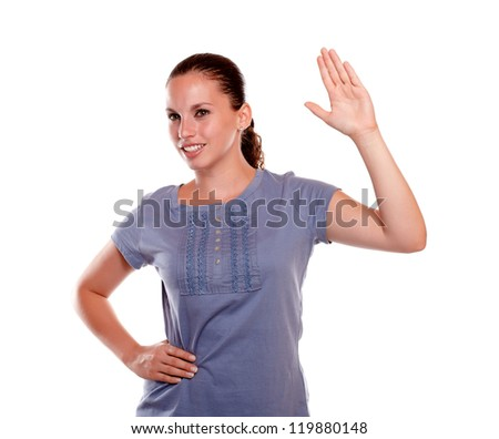 Portrait of a smiling young female greeting to the right on blue shirt standing over white background - stock photo