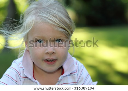 Portrait of a smiling young girl in the garden - stock photo