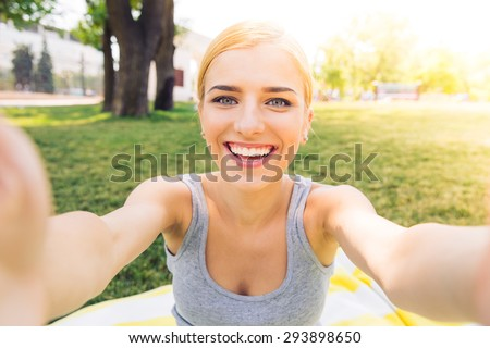 POrtrait of a smiling young girl making selfie photo in park - stock photo