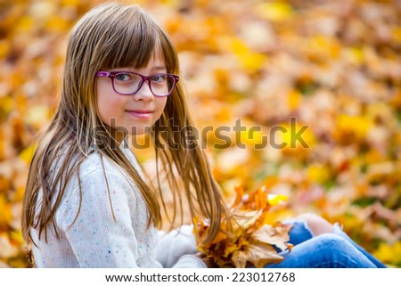 Portrait of a smiling young girl who is holding in her hand a bouquet of autumn maple leaves.Girl sitting on colorful autumn leaves. - stock photo
