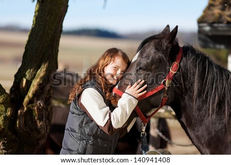 Portrait of a smiling young girl with a dark bay horse with red reins - stock photo
