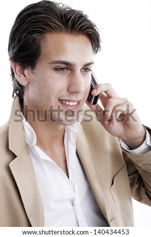 Portrait of a smiling young handsome playboy talking on the mobile phone on a white background