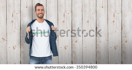 Portrait of a smiling young male volunteer against wooden background