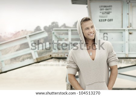Portrait of a smiling young man at the beach - stock photo