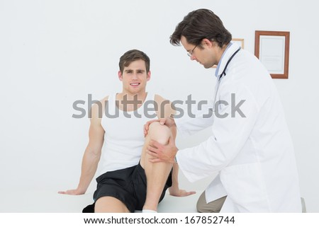 Portrait of a smiling young man getting his knee examined at the medical office - stock photo