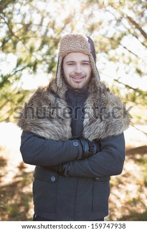 Portrait of a smiling young man in warm clothing standing in forest on a winter day - stock photo
