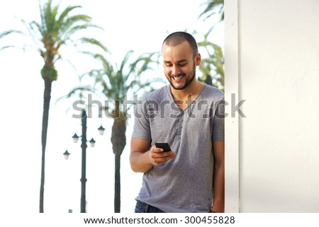 Portrait of a smiling young man reading text message on mobile phone - stock photo