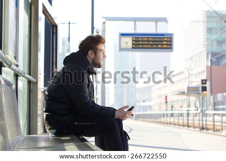 Portrait of a smiling young man sitting on bench at train station - stock photo