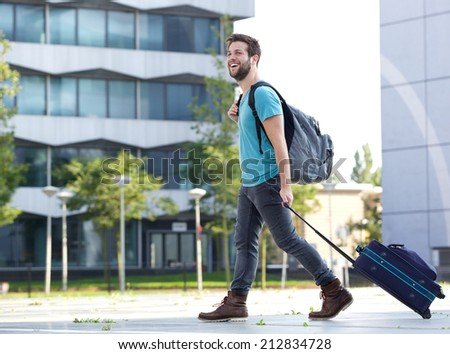 Portrait of a smiling young man traveling with suitcase and bag - stock photo