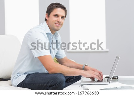 Portrait of a smiling young man using laptop in living room at home