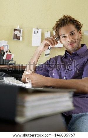 Portrait of a smiling young man with cellphone sitting in the office
