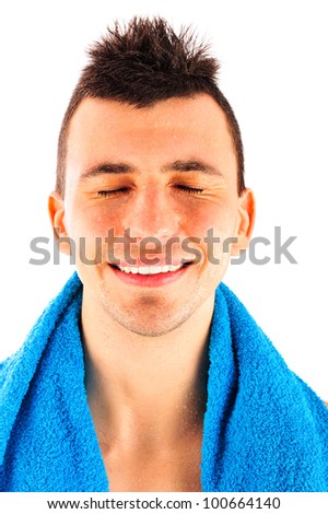 Portrait of a smiling young man with towel around his neck after a workout on white background