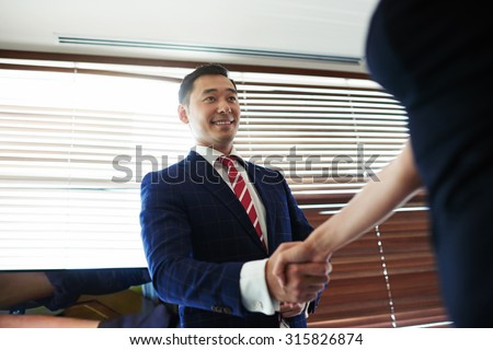 Portrait of a smiling young managing director shaking hands with his business partners while standing in office space interior, asian male entrepreneur enters into an agreement with his new partner - stock photo