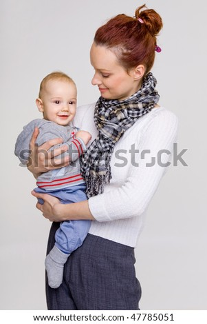 Portrait of a smiling young mother with her adorable baby boy in warm clothes - stock photo