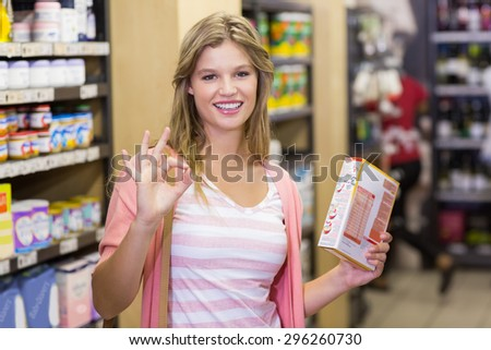 Portrait of a smiling young pretty woman doing a sign of the hand in supermarket - stock photo