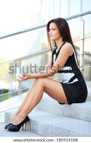 Portrait of a smiling young smart businesswoman having coffee break in office - stock photo